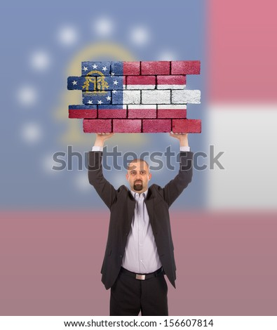 Businessman holding a large piece of a brick wall, flag of Georgia, isolated on national flag - stock photo