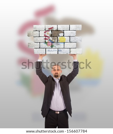 Businessman holding a large piece of a brick wall, flag of Illinois, isolated on national flag - stock photo
