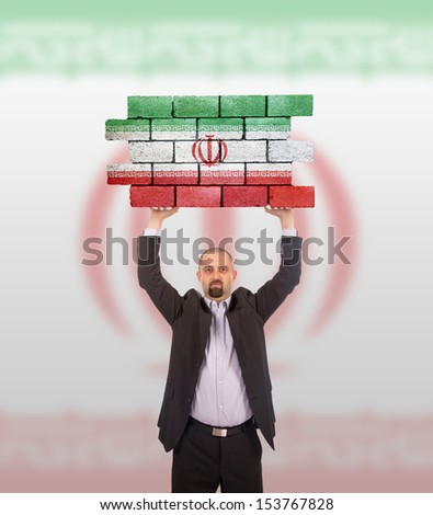 Businessman holding a large piece of a brick wall, flag of Iran, isolated on national flag - stock photo