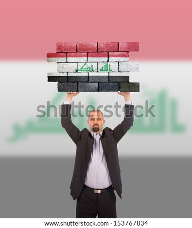 Businessman holding a large piece of a brick wall, flag of Iraq, isolated on national flag - stock photo