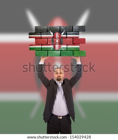 Businessman holding a large piece of a brick wall, flag of Kenya, isolated on national flag - stock photo