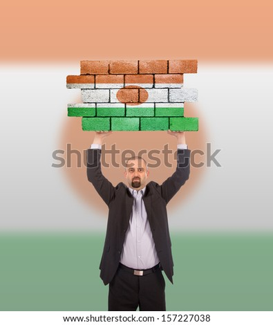 Businessman holding a large piece of a brick wall, flag of Niger, isolated on national flag - stock photo
