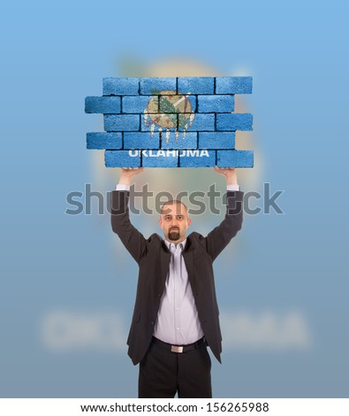 Businessman holding a large piece of a brick wall, flag of Oklahoma, isolated on national flag - stock photo