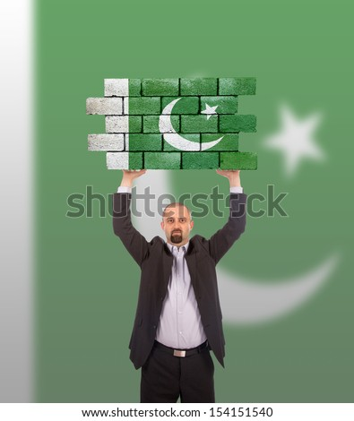 Businessman holding a large piece of a brick wall, flag of Pakistan, isolated on national flag - stock photo