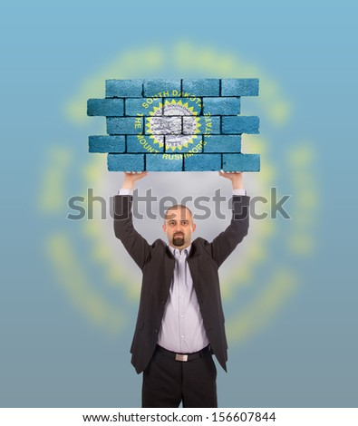 Businessman holding a large piece of a brick wall, flag of South Dakota, isolated on national flag - stock photo