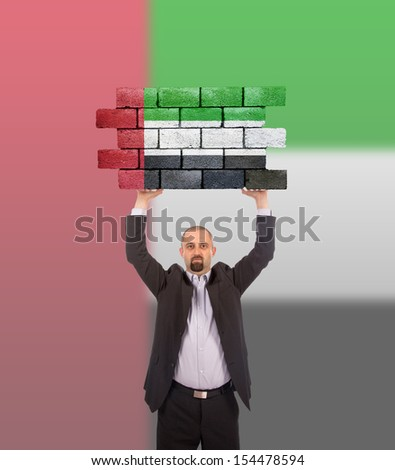 Businessman holding a large piece of a brick wall, flag of the United Arab Emirates, isolated on national flag - stock photo