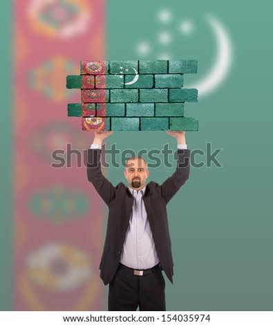 Businessman holding a large piece of a brick wall, flag of Turkmenistan, isolated on national flag - stock photo