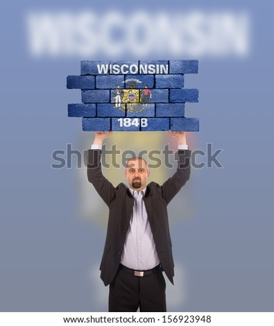 Businessman holding a large piece of a brick wall, flag of Wisconsin, isolated on national flag - stock photo