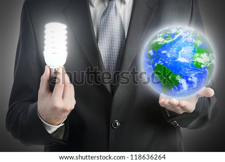 Businessman holding a light bulb and planet Earth. Elements of this image furnished by NASA - stock photo