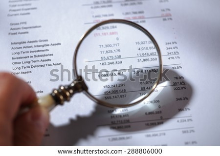 Businessman holding a magnifying glass on a financial report concept for finance, balance sheet, tax or accounting - stock photo