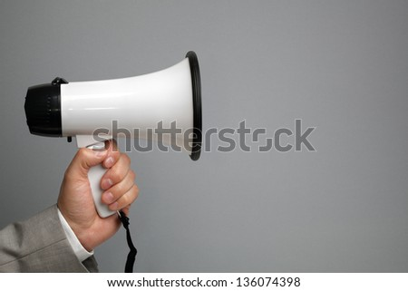 Businessman holding a megaphone in front of blank gray background ready for message - stock photo