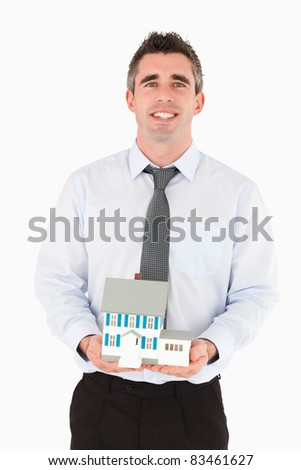 Businessman holding a miniature house against a white background - stock photo