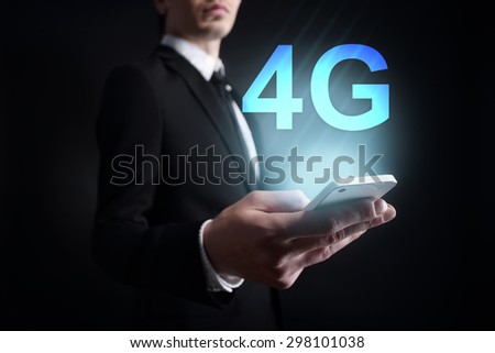 """Businessman holding a mobile phone with """"4G"""" text on virtual screen. Internet concept. Business concept. - stock photo"""