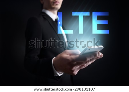 "Businessman holding a mobile phone with ""LTE"" text on virtual screen. Internet concept. Business concept."