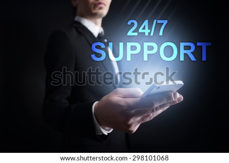 "Businessman holding a mobile phone with ""24/7 support"" text on virtual screen. Internet concept. Business concept. - stock photo"