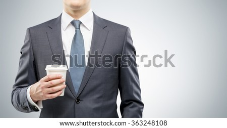 Businessman holding a paper glass of coffee.  Front view, no head. Grey background. Concept of coffee break.