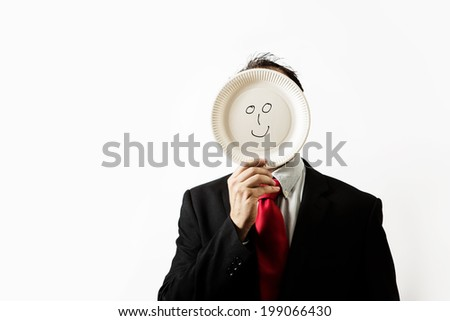 businessman holding a paper plate up to his face with a happy face draw on plate - stock photo