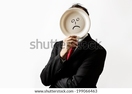 businessman holding a paper plate up to his face with a sad face draw on plate