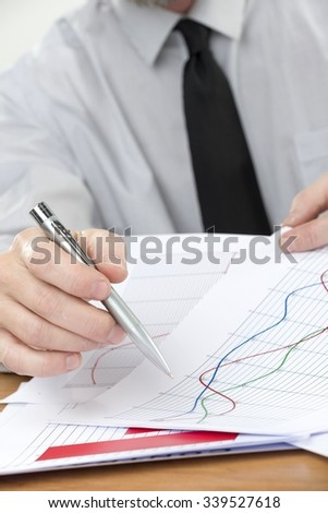 Businessman Holding a Pen and Presenting Draws a Graph