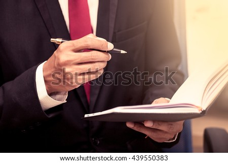 Businessman holding a pen to write on notebook in vintage color tone