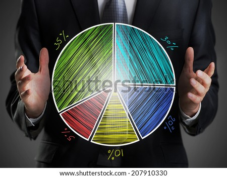 Businessman holding a pie chart - stock photo