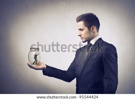 Businessman holding a pot with tiny businessman in it - stock photo
