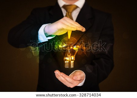Businessman holding a shining light bulb in front of his body