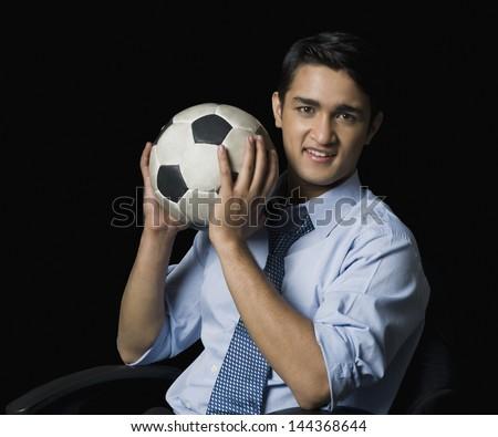 Businessman holding a soccer ball - stock photo