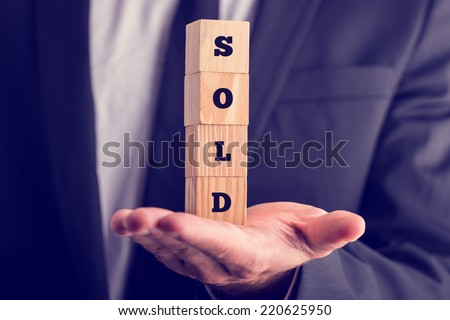 Businessman holding a sold sign composed of stacked wooden blocks balanced on the palm of his hand, conceptual image. - stock photo