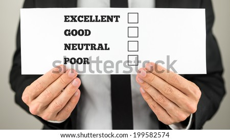 Businessman holding a survey check with multiple choice check boxes for excellent - good - neutral - poor ratings. - stock photo