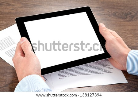 businessman holding a tablet computer with isolated screen on the table with documents - stock photo