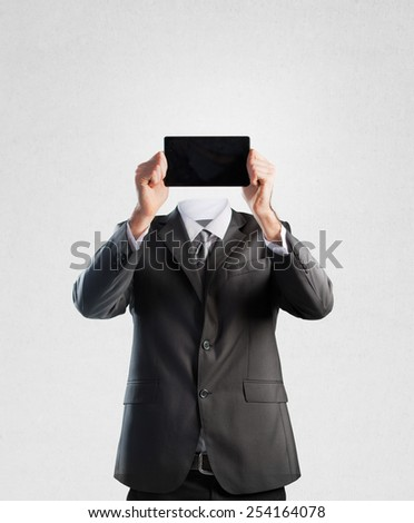 Businessman holding a tablet instead of his head - stock photo