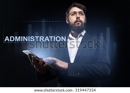"""Businessman holding a tablet pc with """"Administration"""" text on virtual screen. - stock photo"""