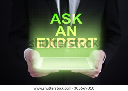 "Businessman holding a tablet pc with ""ask an expert"" text on virtual screen. Business concept. Internet concept. - stock photo"
