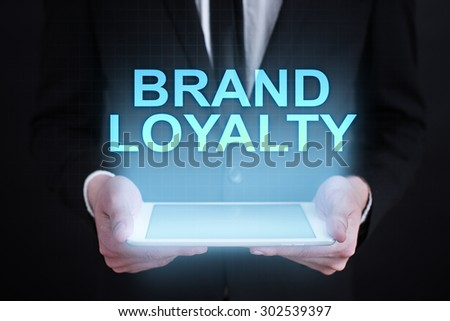"Businessman holding a tablet pc with ""Brand loyalty"" text on virtual screen. Business concept. Internet concept."