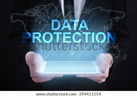 """Businessman holding a tablet pc with """"Data protection"""" text on virtual screen. Internet concept. Business concept. - stock photo"""
