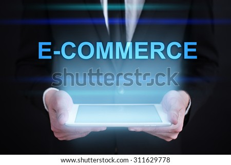 "Businessman holding a tablet pc with ""E-commerce"" text on virtual screen. Internet concept. Business concept."