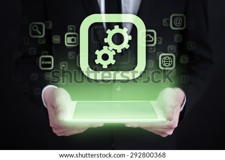 Businessman holding a tablet pc with gears icon on virtual screen. Business concept. - stock photo