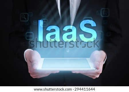 """Businessman holding a tablet pc with """"iaas"""" text on virtual screen. Internet concept. development.  - stock photo"""