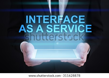 """Businessman holding a tablet pc with """"Interface as a service"""" text on virtual screen. Internet concept. Business concept.  - stock photo"""