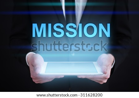 "Businessman holding a tablet pc with ""Mission"" text on virtual screen. Internet concept. Business concept.  - stock photo"