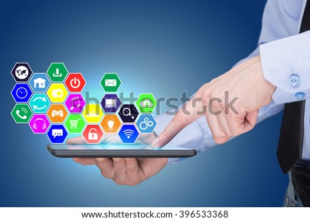 Businessman holding a tablet pc with mobile applications icons on virtual screen . Internet and business concept.