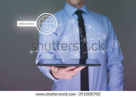 Businessman holding a tablet pc with online service text on virtual screen. Internet concept.  - stock photo