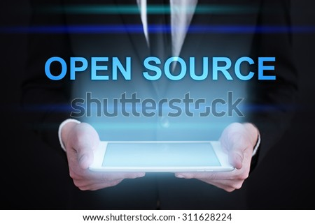 "Businessman holding a tablet pc with ""Open source"" text on virtual screen. Internet concept. Business concept."