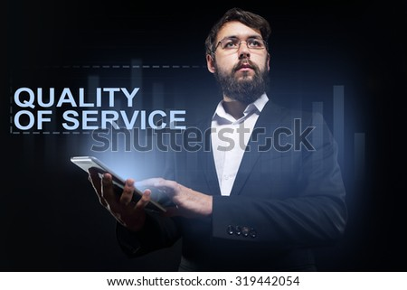 """Businessman holding a tablet pc with """"Quality of service"""" text on virtual screen. Business concept. - stock photo"""