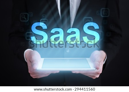 """Businessman holding a tablet pc with """"Saas"""" text on virtual screen. Internet concept. development.  - stock photo"""
