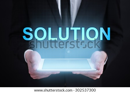 "Businessman holding a tablet pc with ""solution"" text on virtual screen. Business concept. Internet concept. - stock photo"
