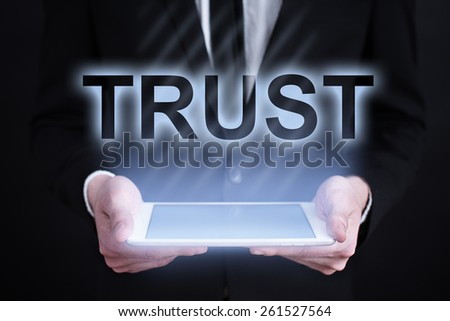 Businessman holding a tablet pc with trust text on virtual screen . Internet concept. business concept. - stock photo
