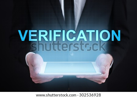 "Businessman holding a tablet pc with ""verification"" text on virtual screen. Business concept. Internet concept."