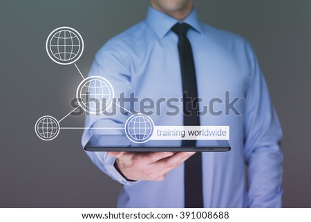 Businessman holding a tablet pc with worldwide training text on virtual screen. Internet and Business concept. - stock photo